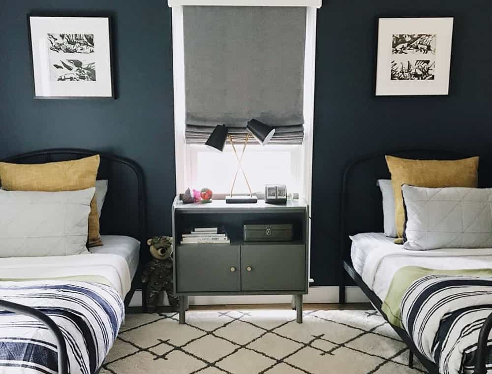 Boys bedroom with two twin beds against a navy blue wall and a grey roman shade in the window in the middle.