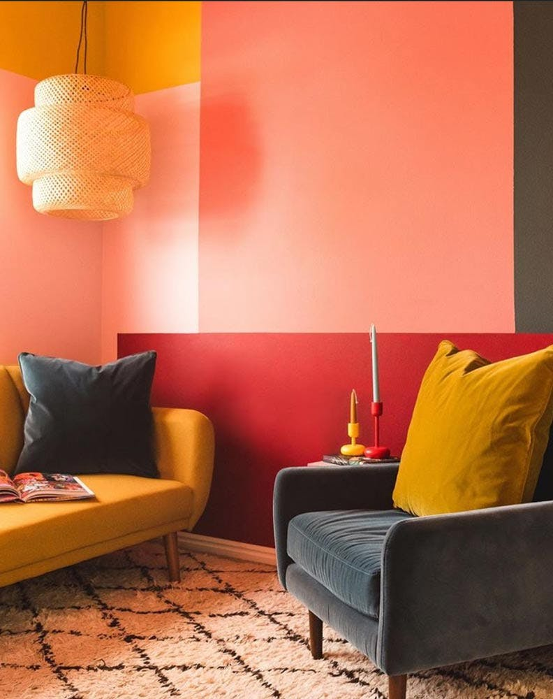 a sofa and arm chair in a corner of a pink and red painted color blocked room.