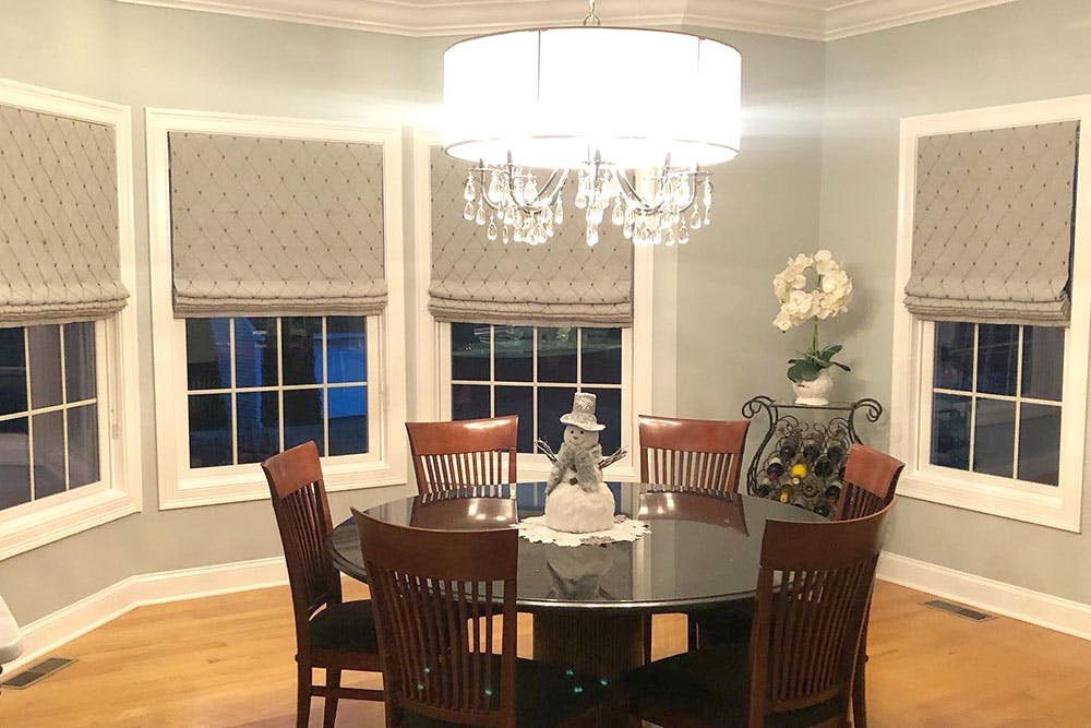 dining room table near a set of bay windows covered with roman shades.