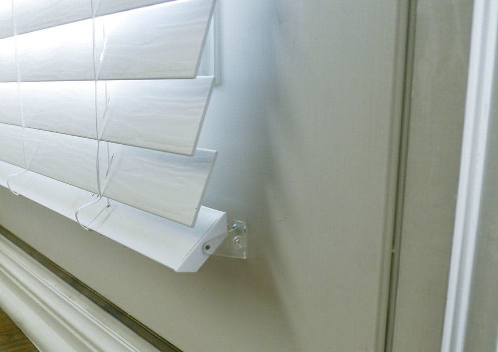 white blinds on door with hold down bracket