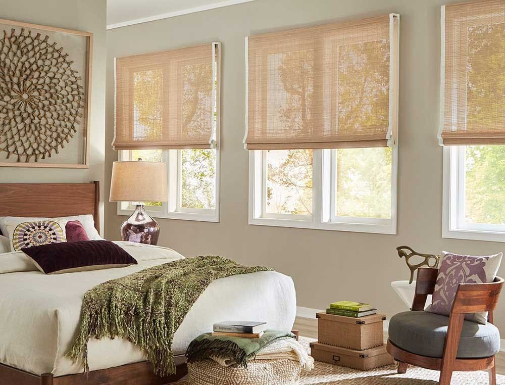 Bedroom with three large windows covered by woven wood shades.