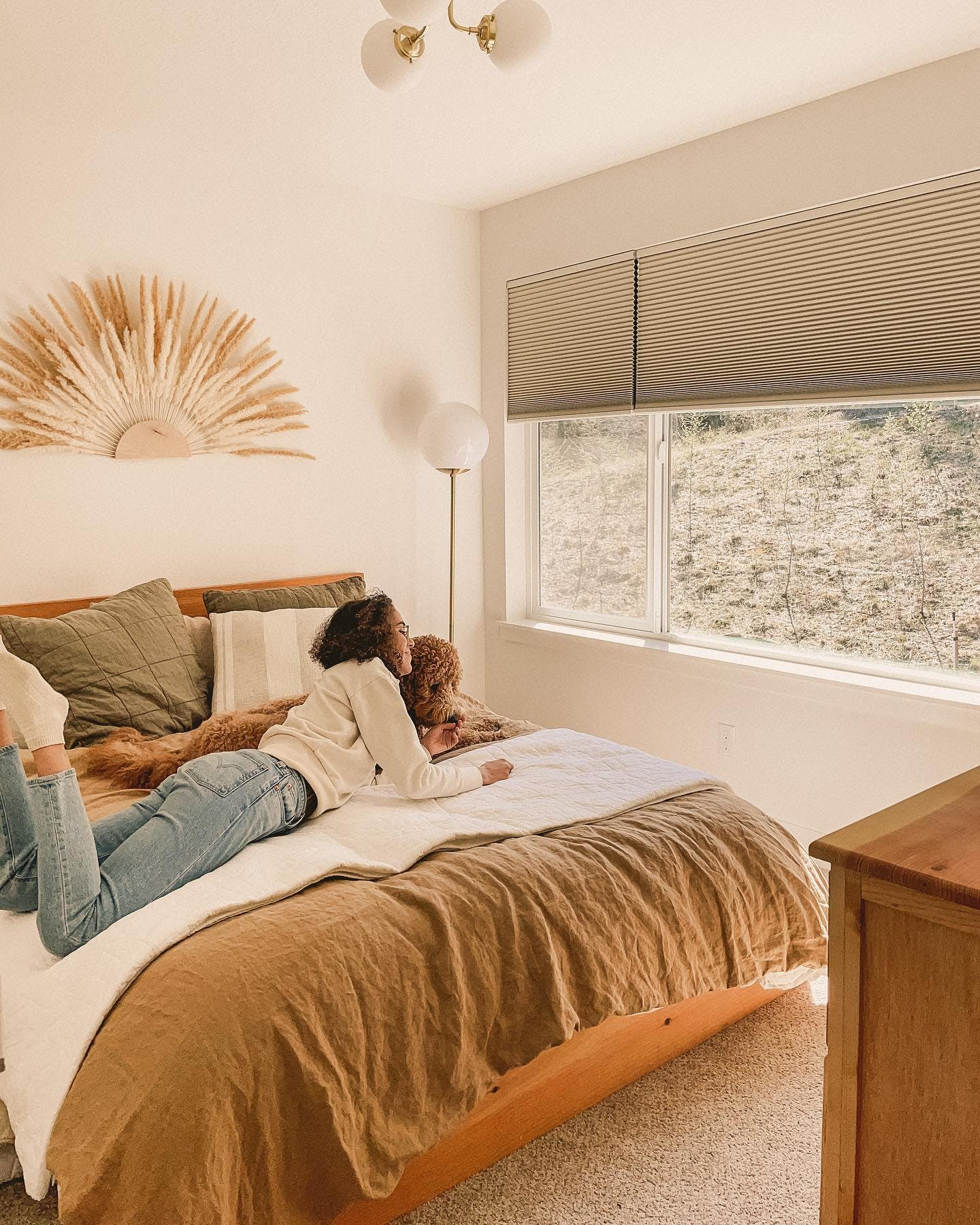 woman lays on bed with dog looking out window with blackout window shades