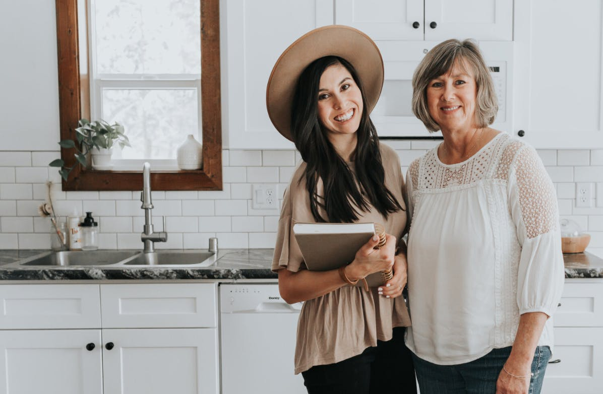 Jessie and Stacey of the goodnight house standing in front of a kitchen sink and window