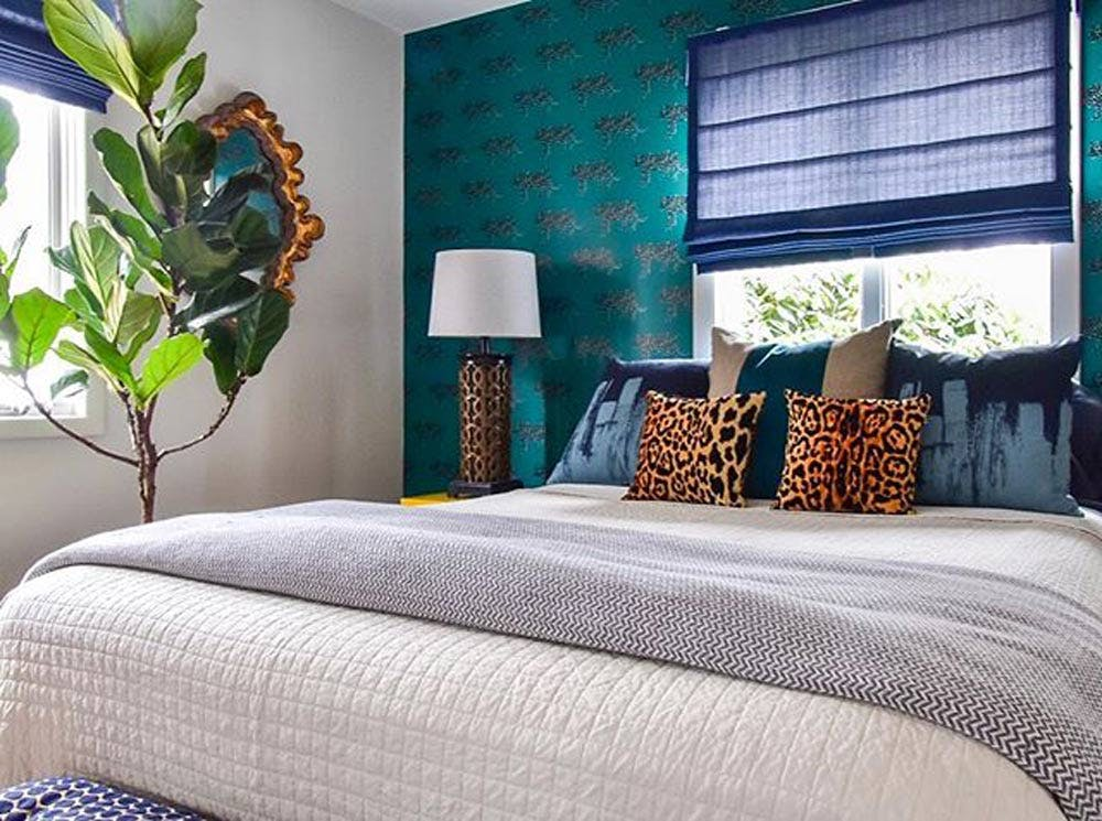 Modern eclectic bedroom with wallpaper and a blue roman shade behind bed.