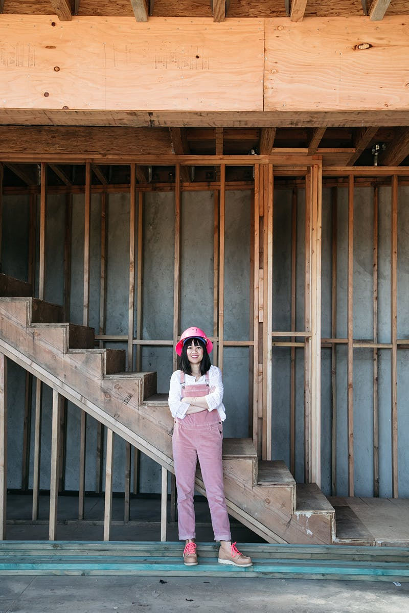 Joy cho wearing pink overalls standing in front of stairs on construction site