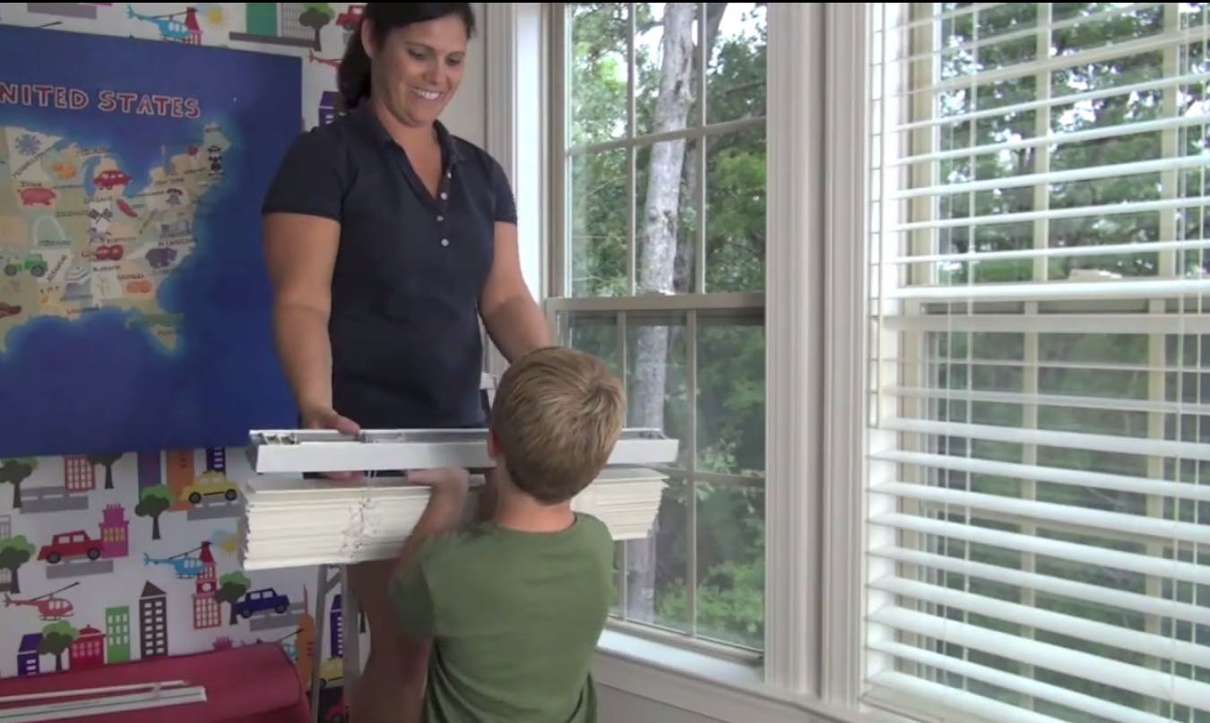 young boy helping mother install blinds