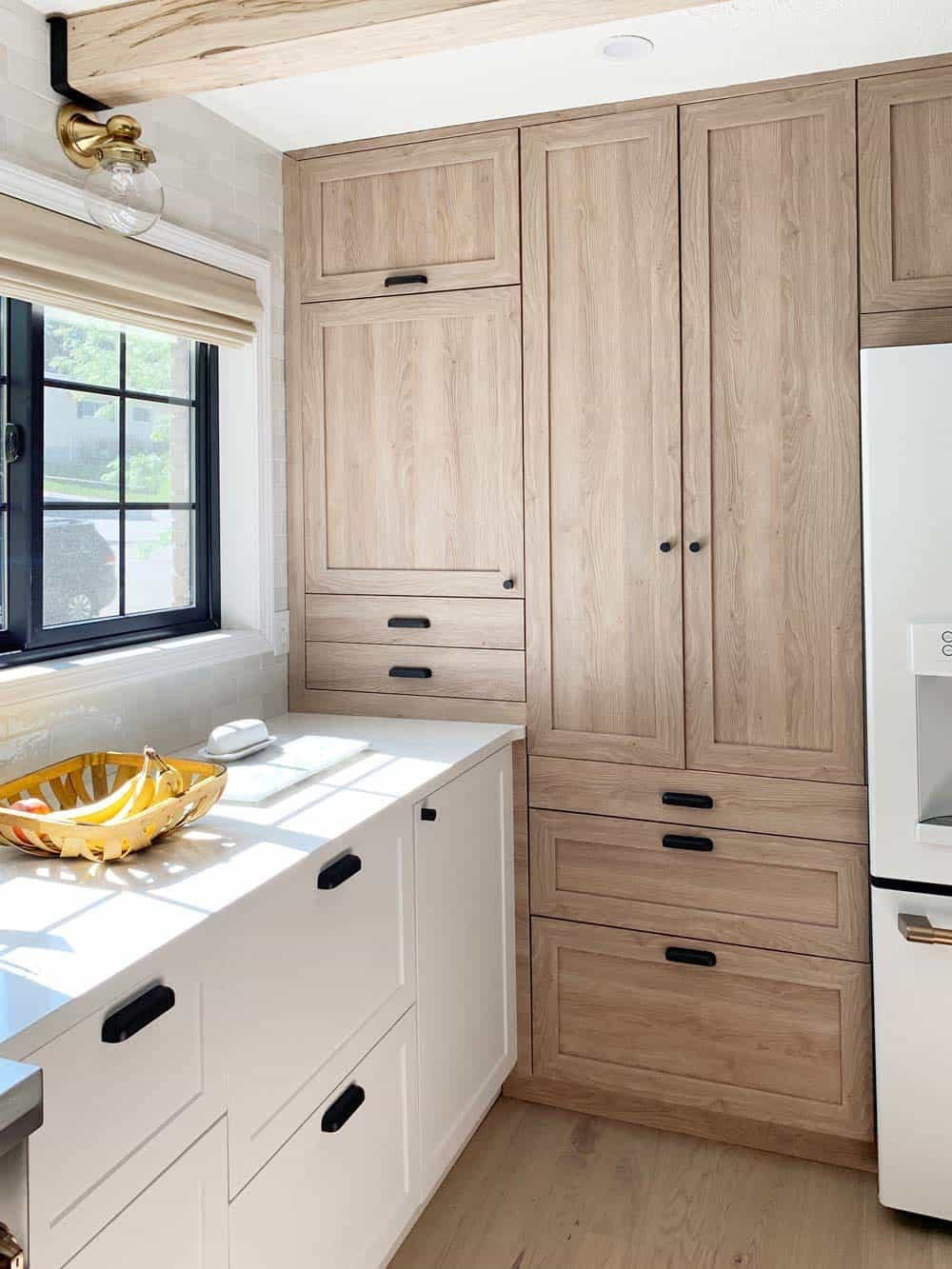 Light wood toned kitchen cabinets with matching woven wood shade in window.