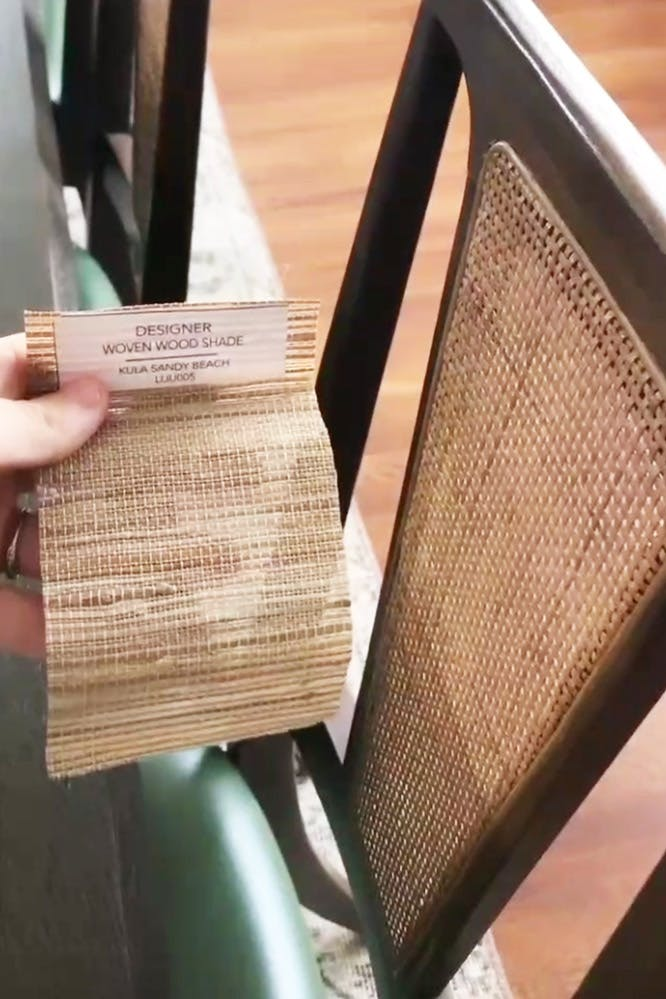 Woven wood sample held next to rattan backed chair for color comparison.