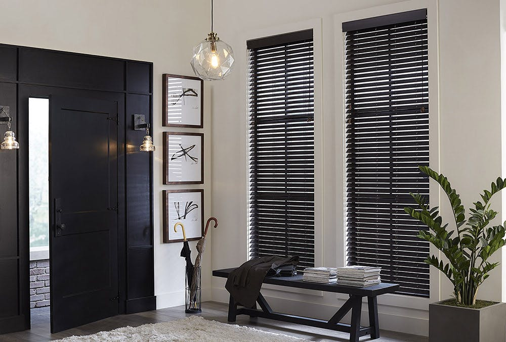 Modern entry way with black door, black bench and black faux wood blinds.
