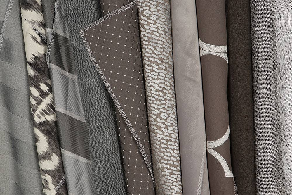 Grey roman shade fabrics rolled and lined up next to each other.