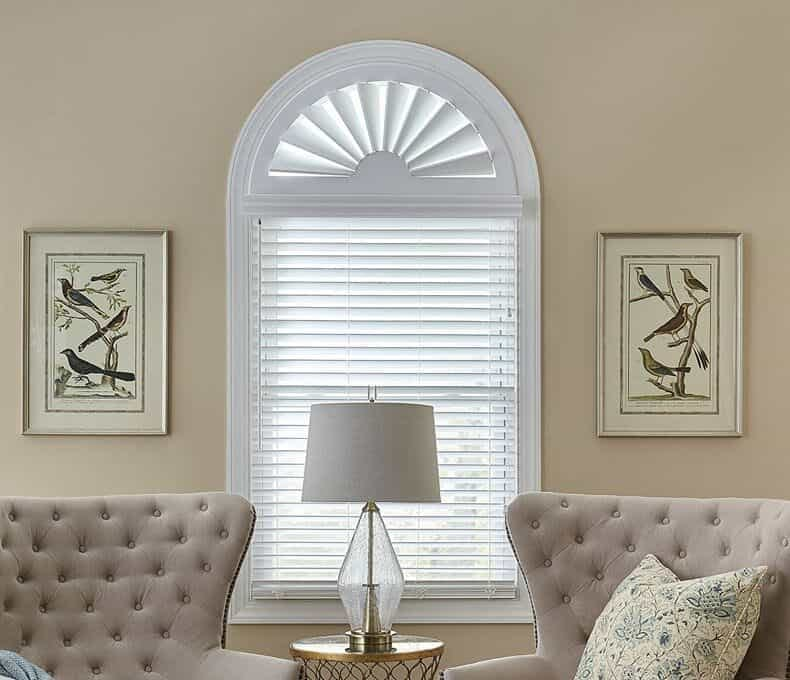 Arched window with a specialty shaped shutter covering the top and a blind in the bottom section.