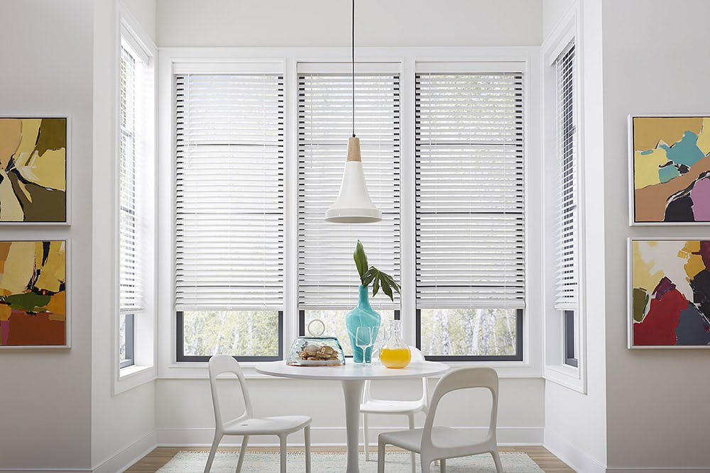 Sunny, white kitchen nook with a small table, two chairs, a pitcher of orange juice and plate of pastries.