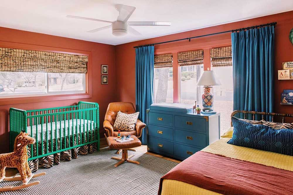 Colorful terracotta red and blue kid's room with woven wood shades in the windows.