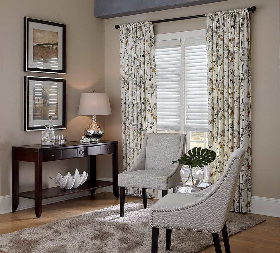 Traditional living room with white blinds and floral draperies.