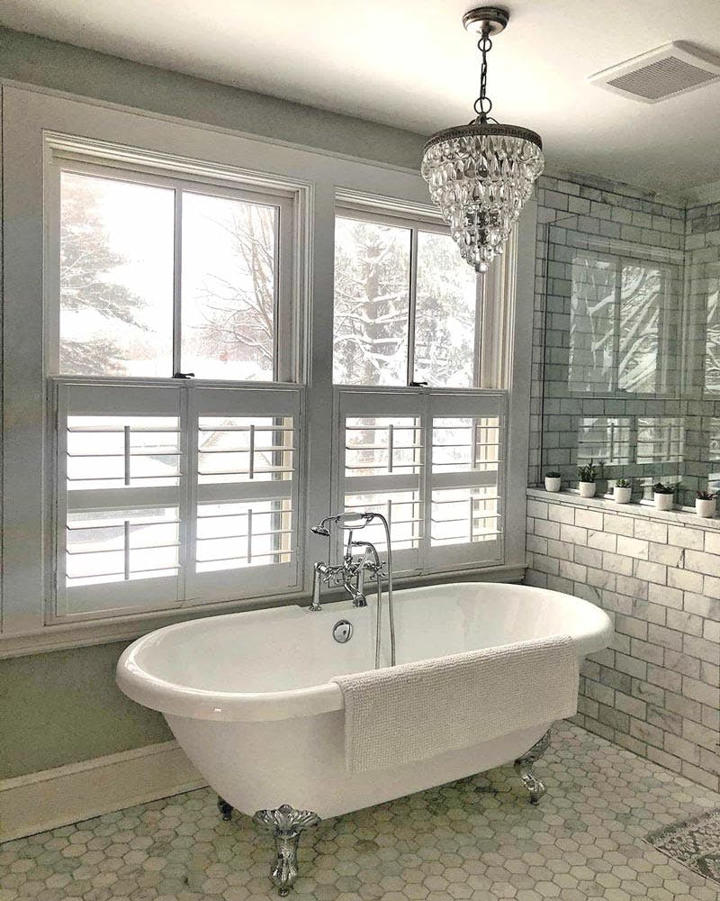 Contemporary tiled bathroom with shiny clawfoot tub and cafe height shutters over windows that look out onto a snowy field.