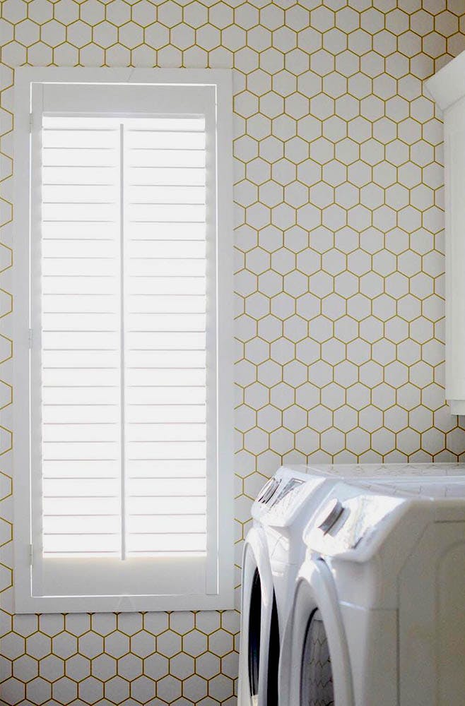 bright laundry room with white and gold hexagon wallpaper and a white shutter in the window.
