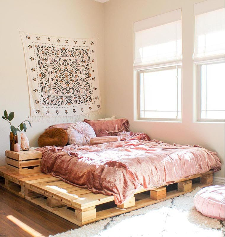 Sunny boho girls bedroom with pink velvet pallet bed and white woven wood shades in the windows.