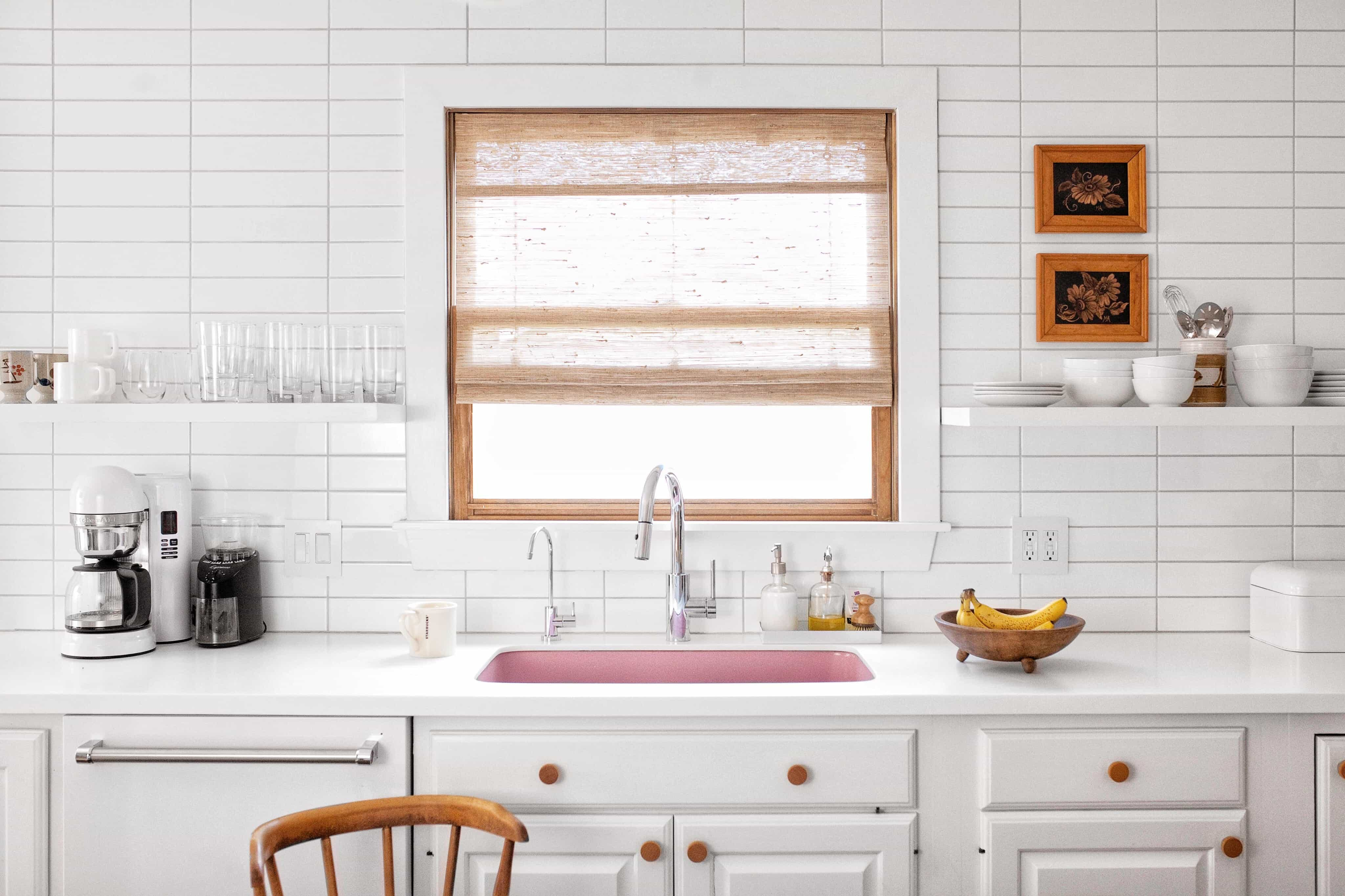 70s inspired, white kitchen with pink sink and woven wood shades in the window.