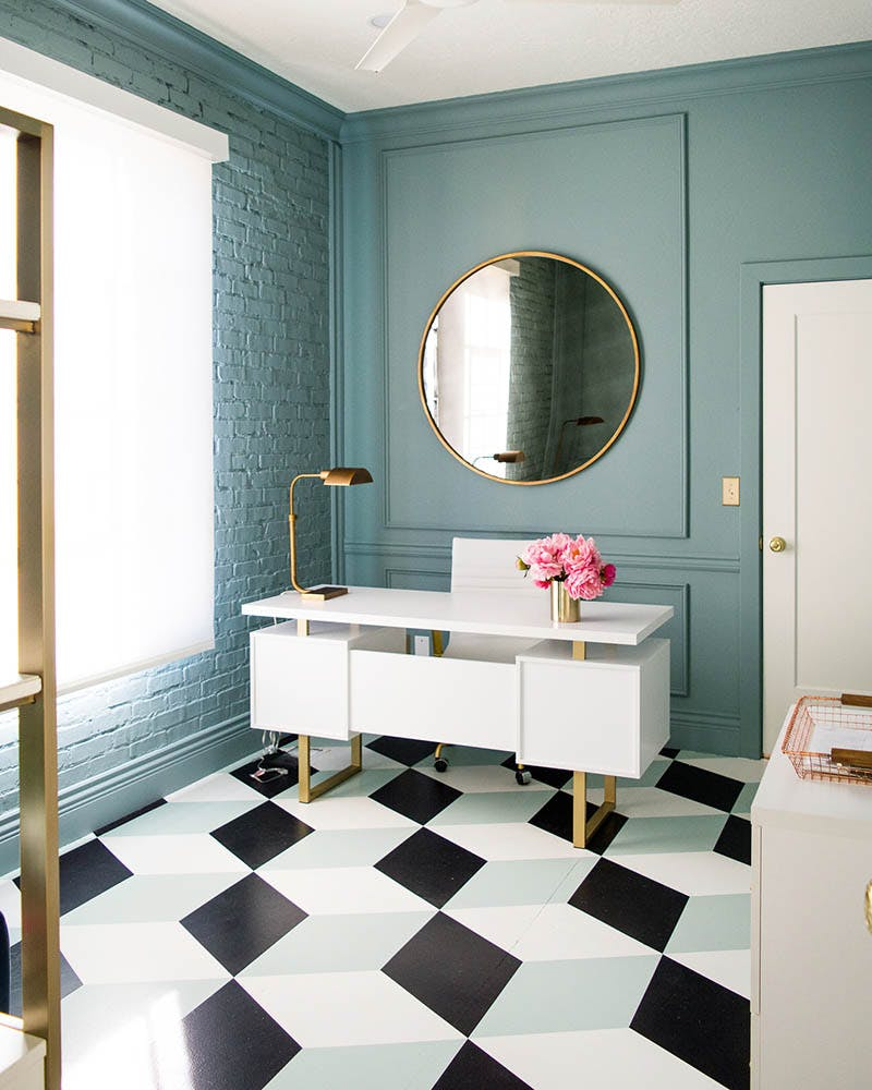 teal, retro inspired office with geometric floor tiles, a white desk and brass accents.