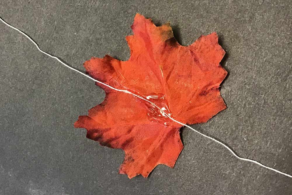 Close up of fabric leaf with string hot glued to back of it