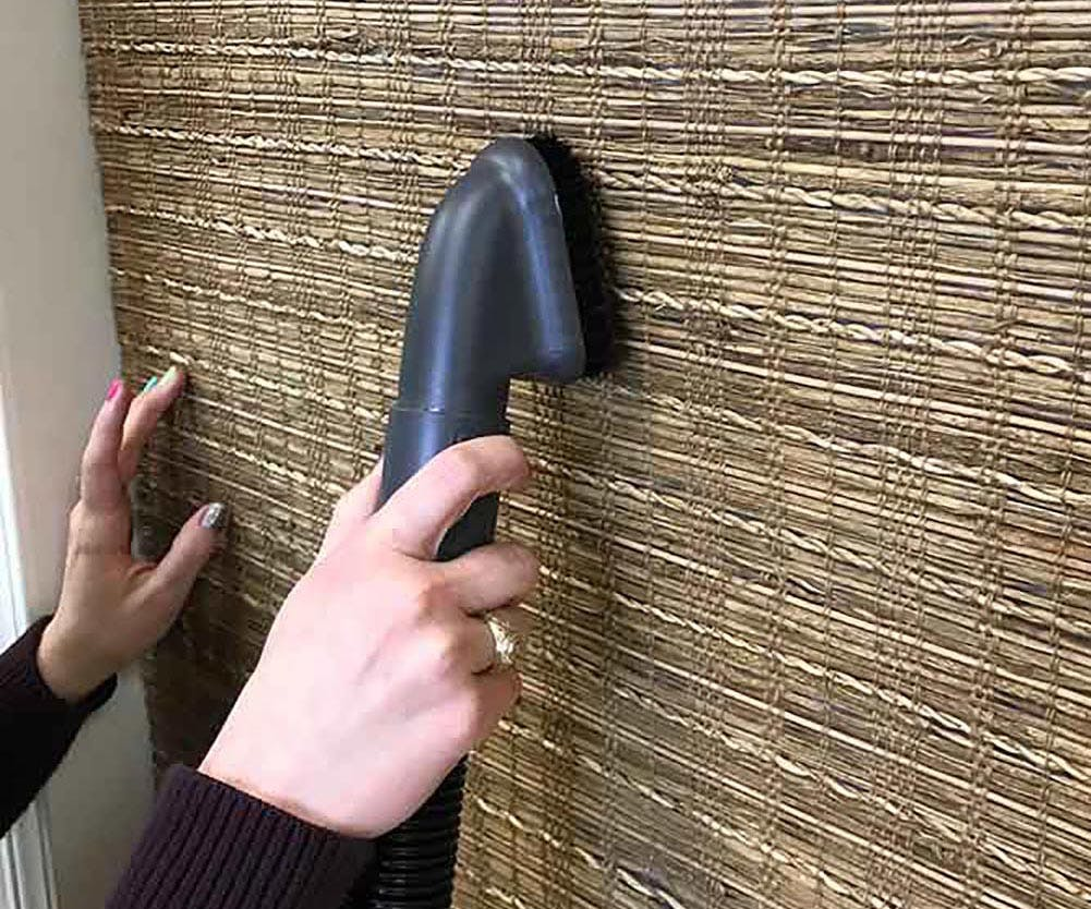 Close up of woven wood shades being vacuumed with the brush attachment.