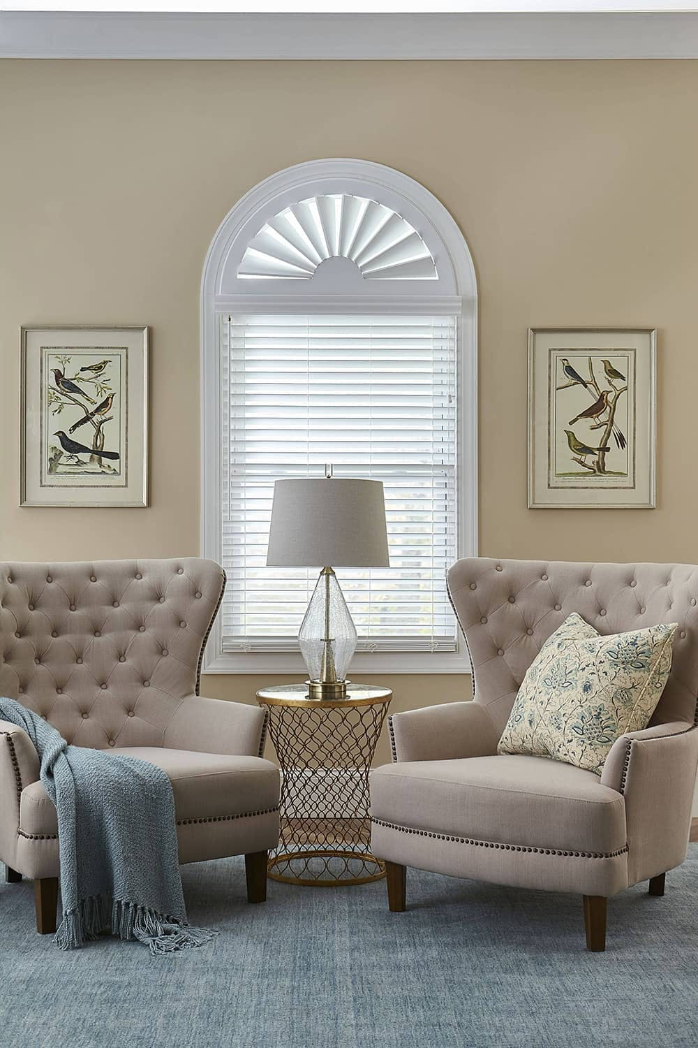 two upholstered chairs in front of arch window with blinds and arch shutter