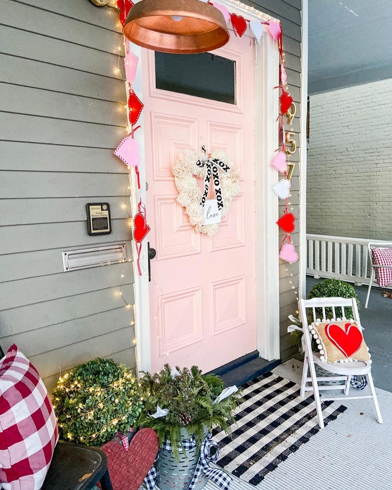 Pastel pink front door with red and white valentines day garland.