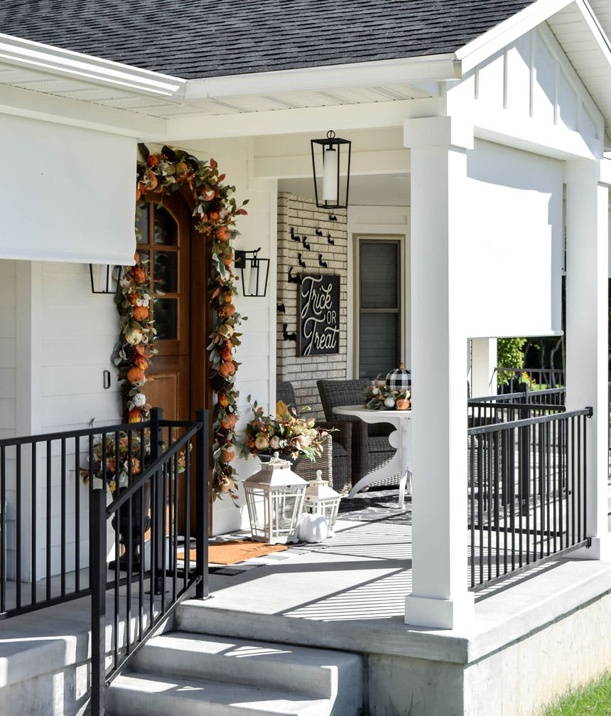 porch decorated for fall with roll down solar shades