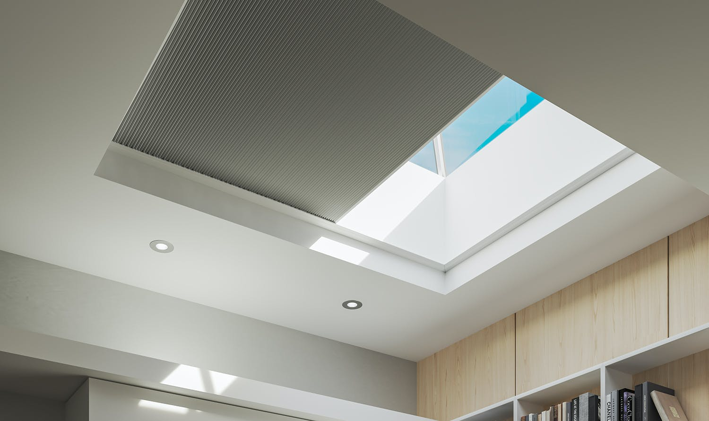 modern, sunny skylight window with a grey blackout cellular shade half way closed.