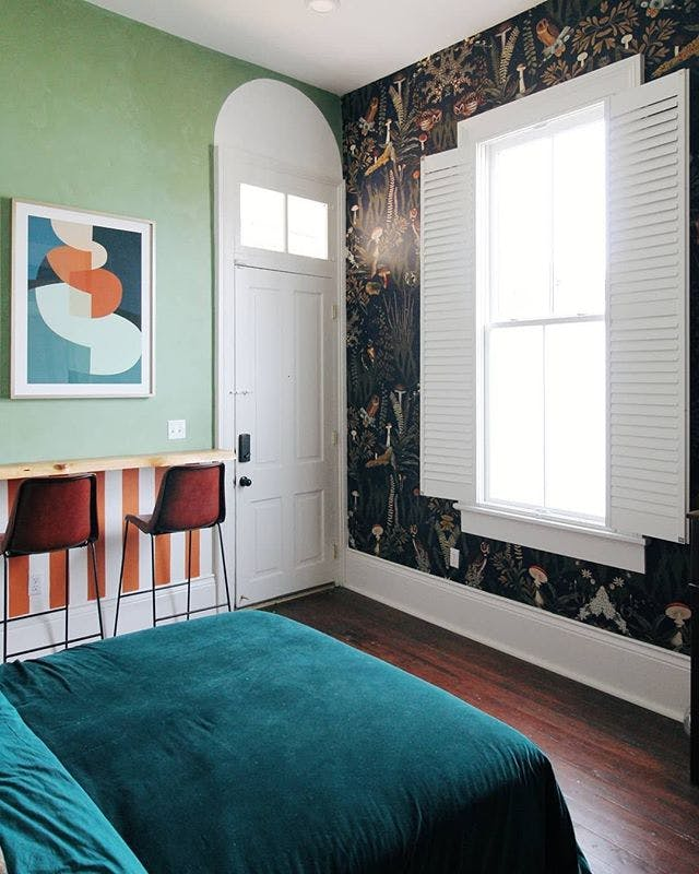 Modern eclectic bedroom with floral wallpaper and plantation shutters.