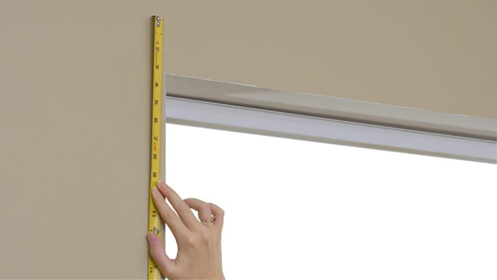 Measuring the height of a window with a steel tape measure.