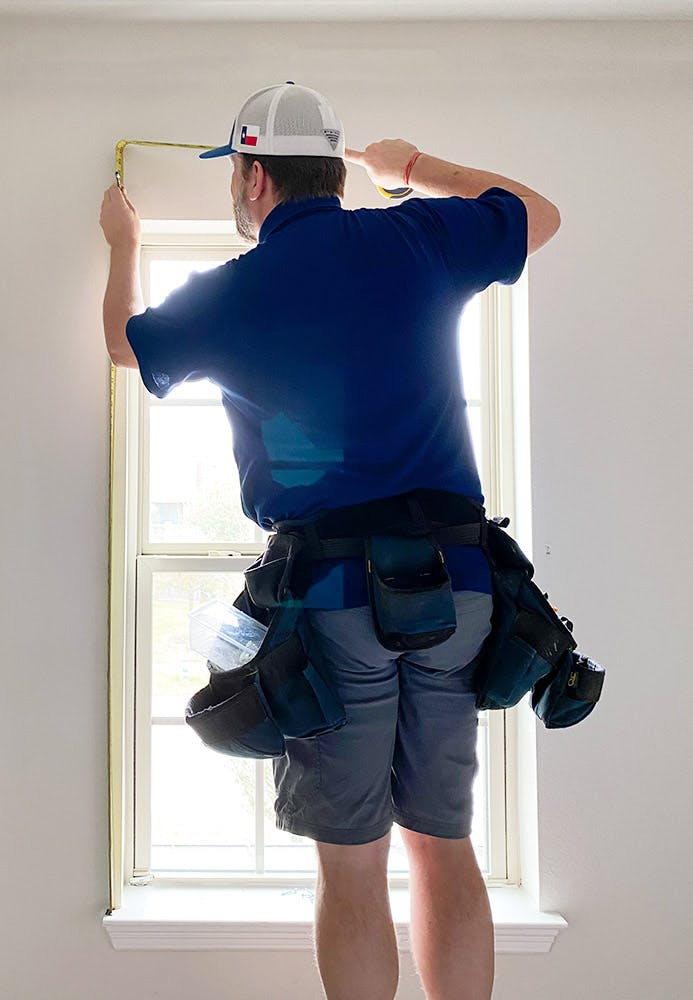 Man wearing blue shirt and tool belt stands on a ladder to measure a window's height.