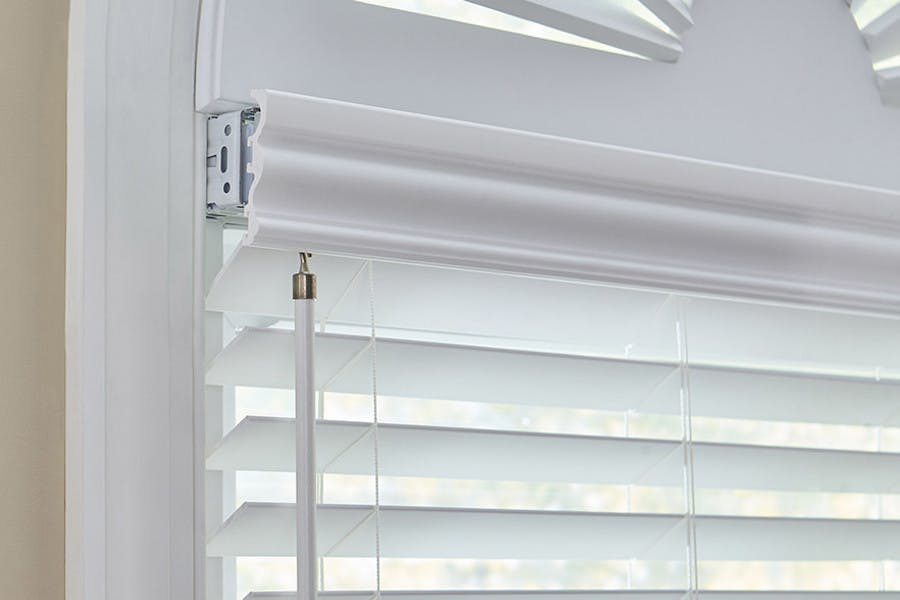 A white faux wood blind partially recessed in window without much depth so the hardware is exposed.