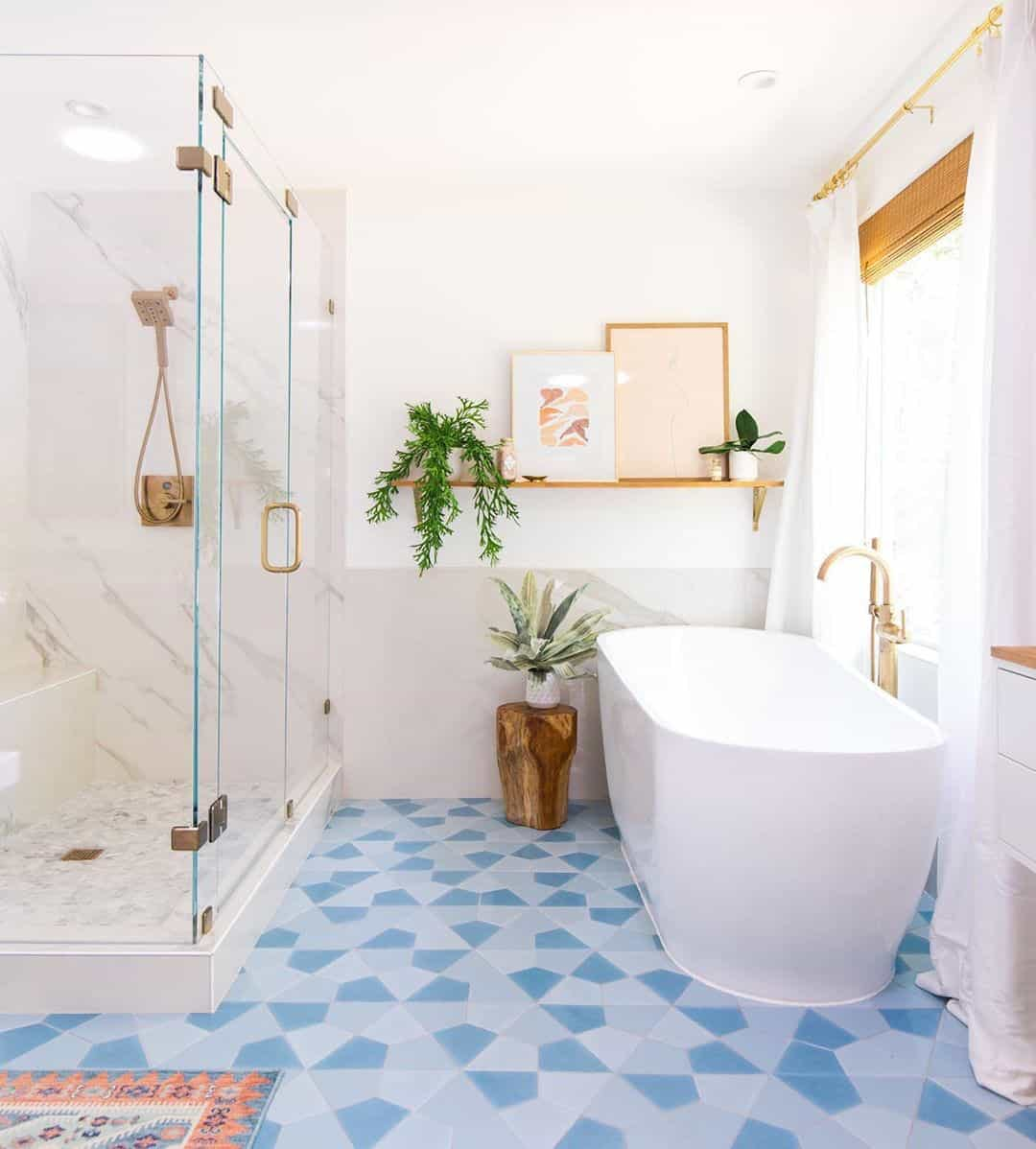 Bright and airy bathroom with colorful, geometric blue tiles, oversized tub and woven wood shades in the window.