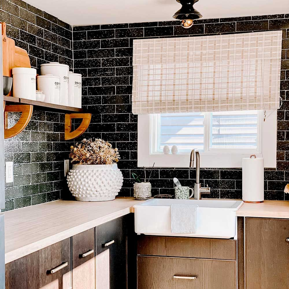 Farmhouse kitchen sink with black subway tile backsplash, white countertops, wood shelving and beige roman shades on the window above the sink.