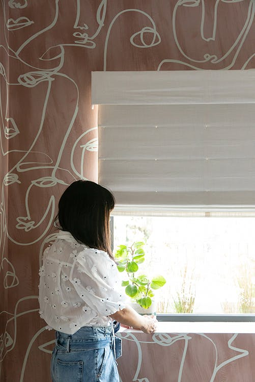 woman looking out window in room with pink wallpaper and white roman shades