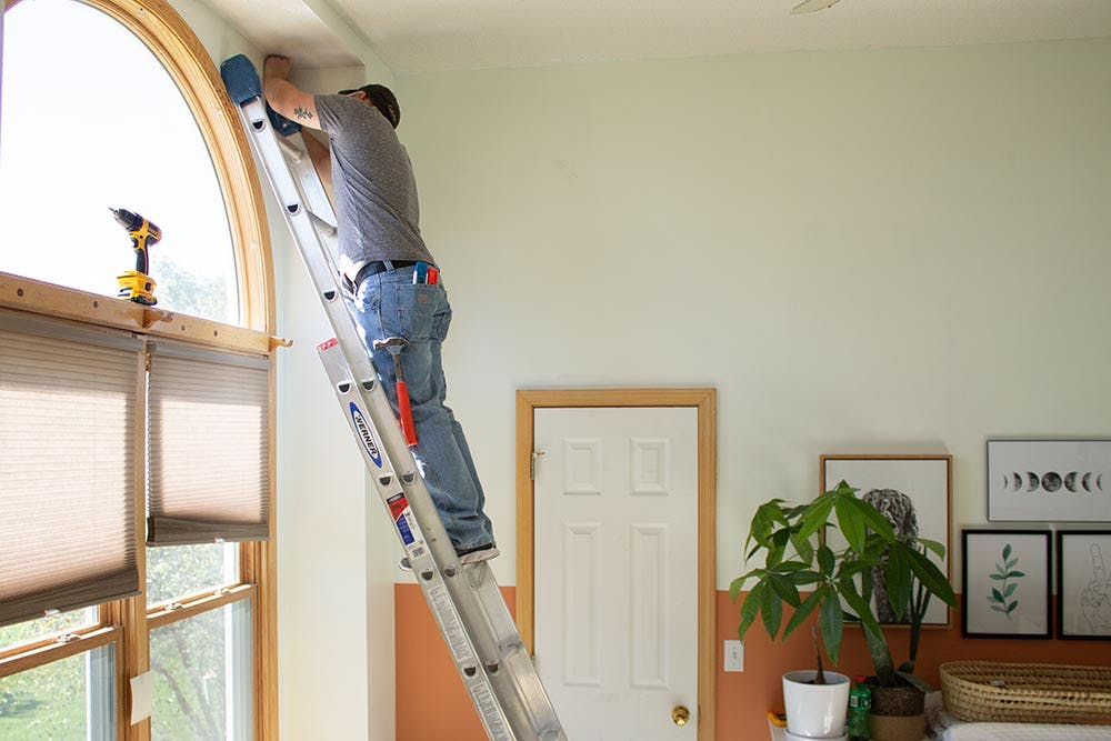 Man standing on a ladder, installing roller shade brackets into a tall ceiling in front of an arch window.