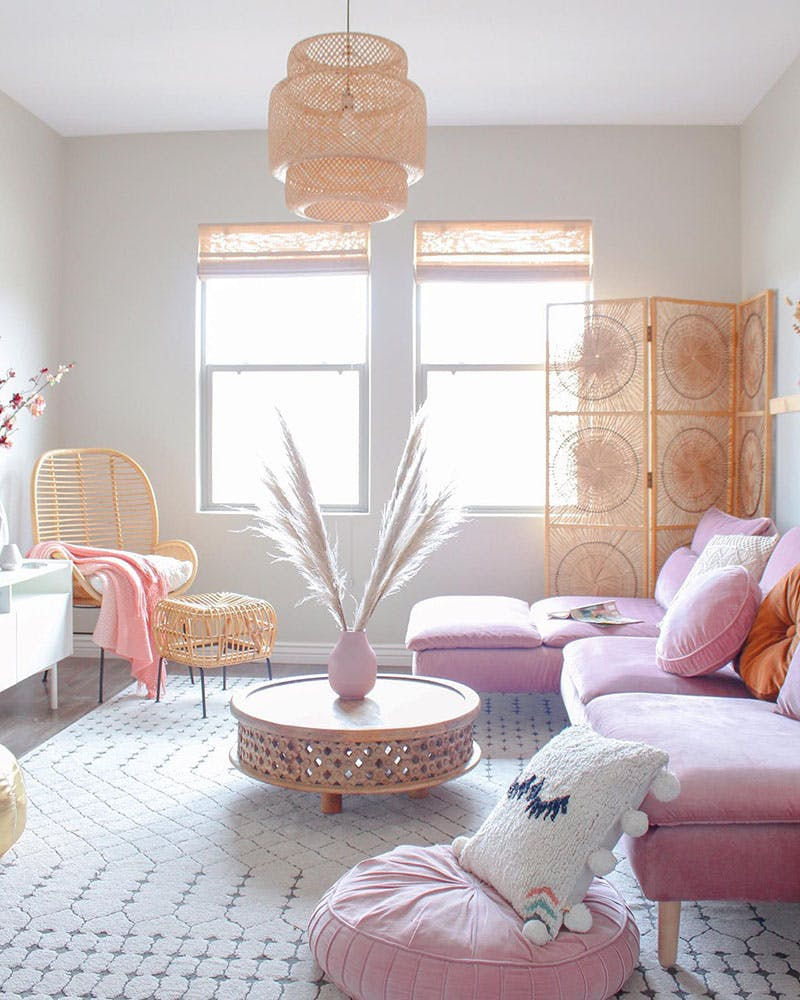 bright white living room with pink furniture and light woven wood shades and wicker accessories.