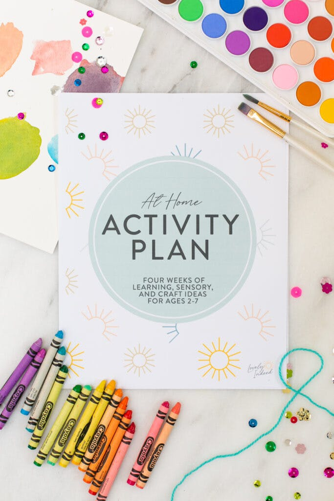 flat lay with crayons, paints and kids activity plan booklet