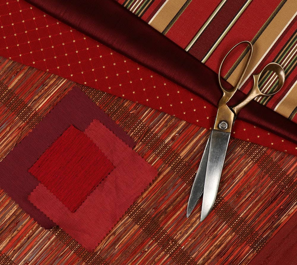 flatlay with red roman shade fabrics and antique brass scissors.