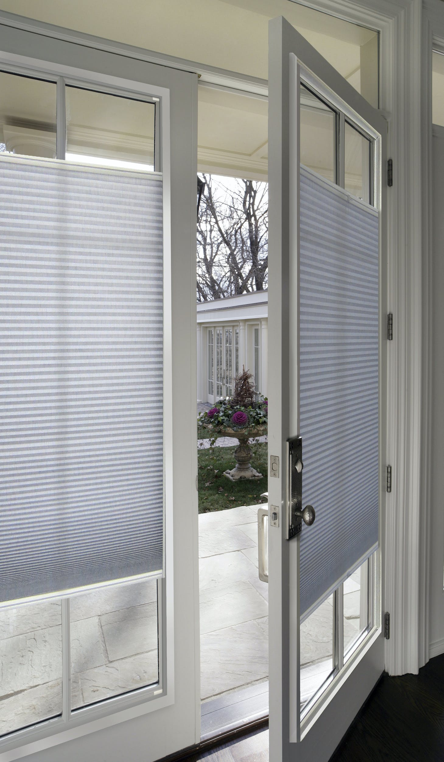 french doors with white cellular shades installed over the glass.