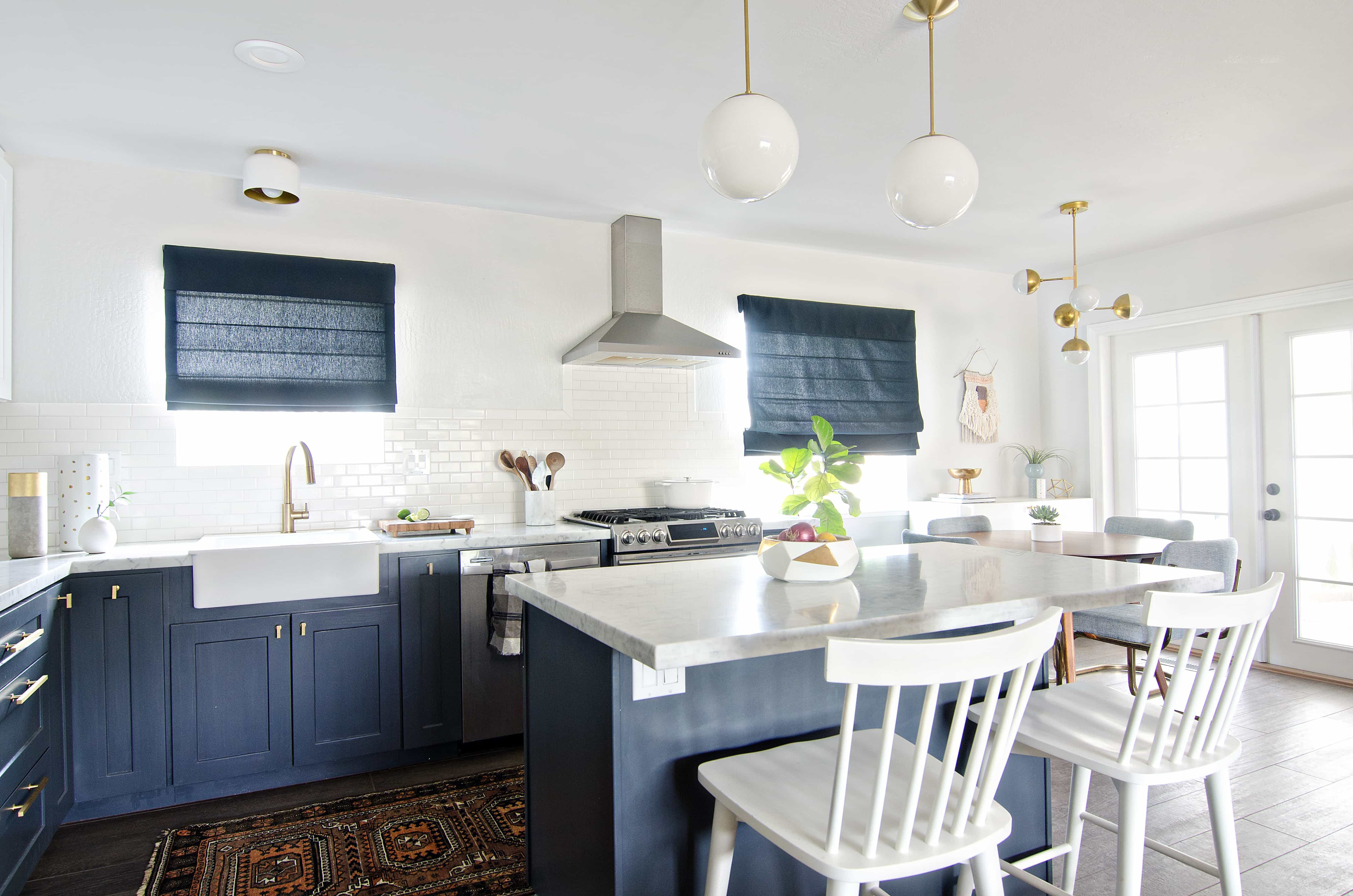 Bright kitchen with white walls and blue cabinets and blue roman shades.