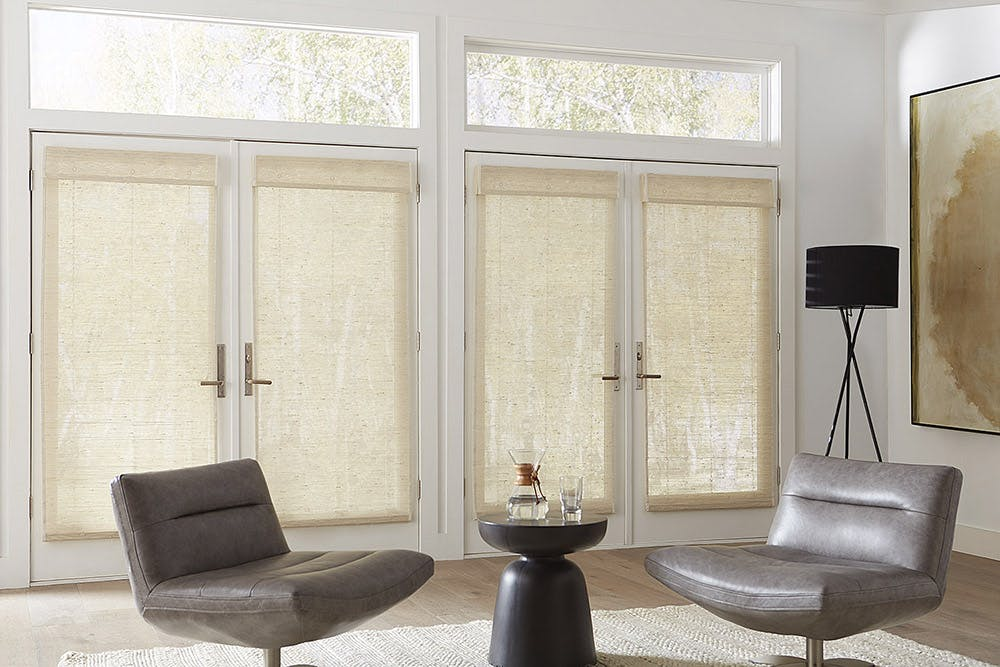 modern living room with two sets of french doors and woven wood shades.
