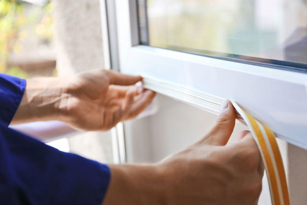 a person installs weather stripping over the seams on a window.