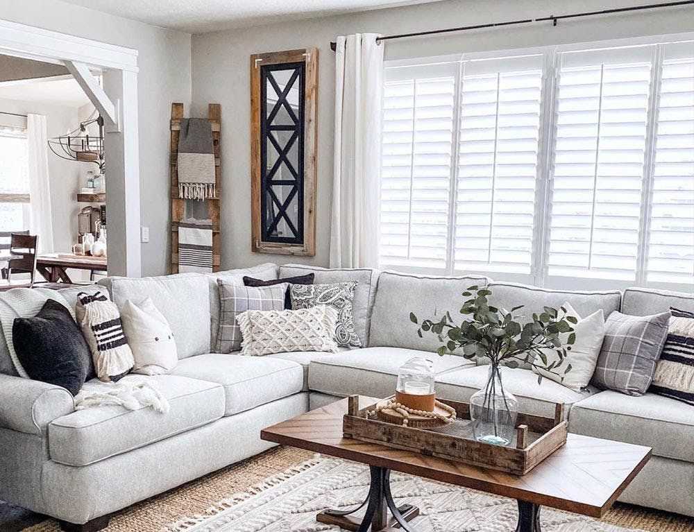 Contemporary, modern farmhouse living room with plantation shutters in the windows.