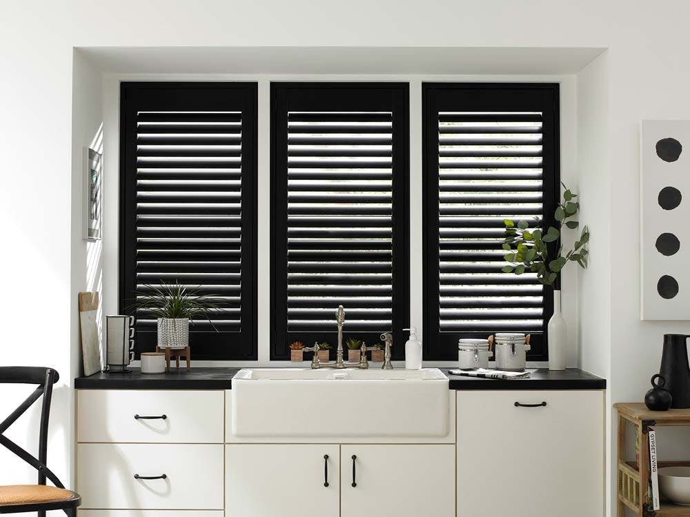Black and white modern kitchen with black plantation shutters in windows over the sink.