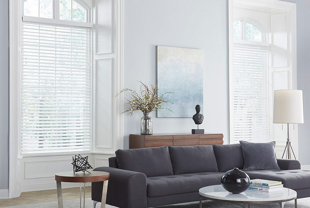 modern living room with white faux wood blinds in large windows.