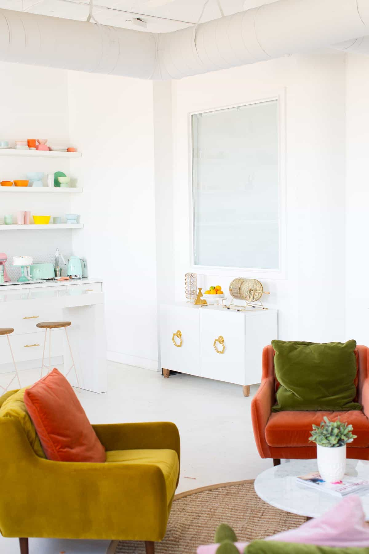 White walled office with retro, velvet furniture in green, burn orange and marigold colors.