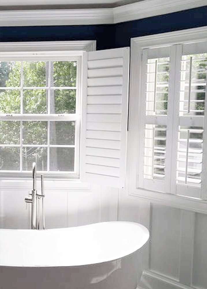 bathroom bay window over freestanding tub with shutters over the windows.