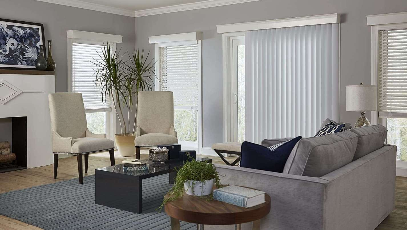 Greige living room with vertical blinds over the sliding glass door.